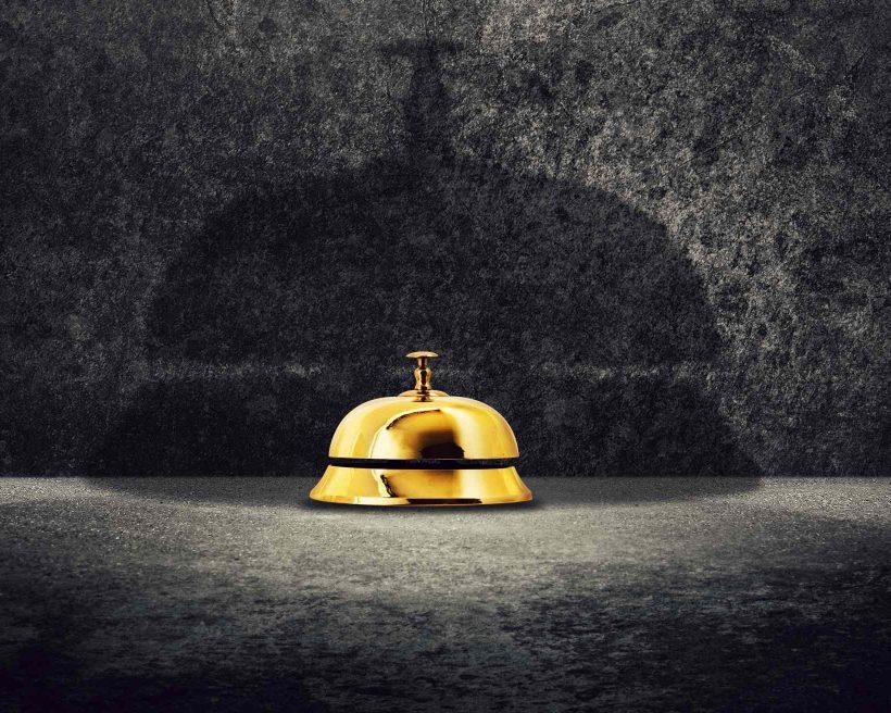 Brass hotel reception bell on ground