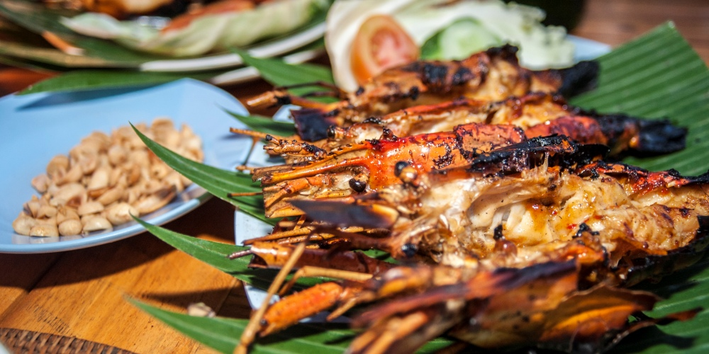 Grilled lobster on the shell sitting on a banana leaf.