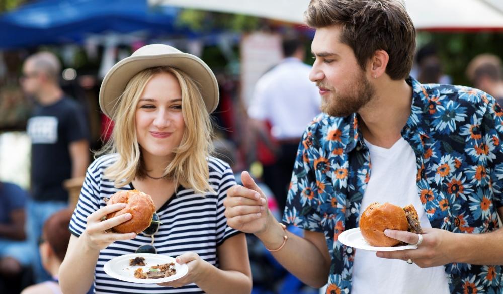 Couple eating burgers at food market