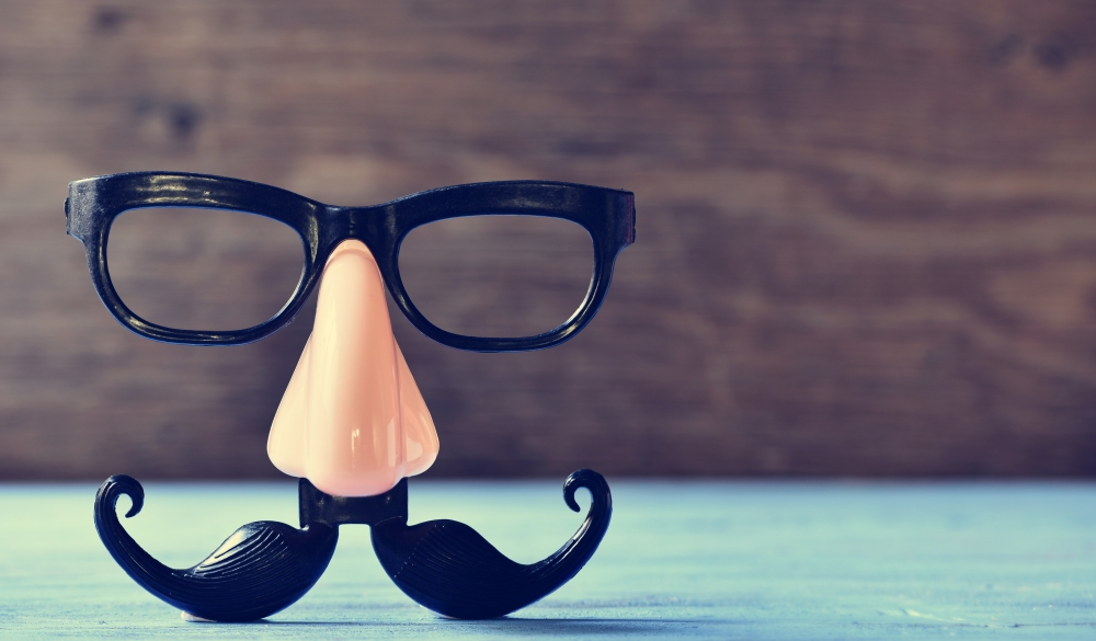 a fake mustache, nose and eyeglasses on a rustic blue wooden surface;