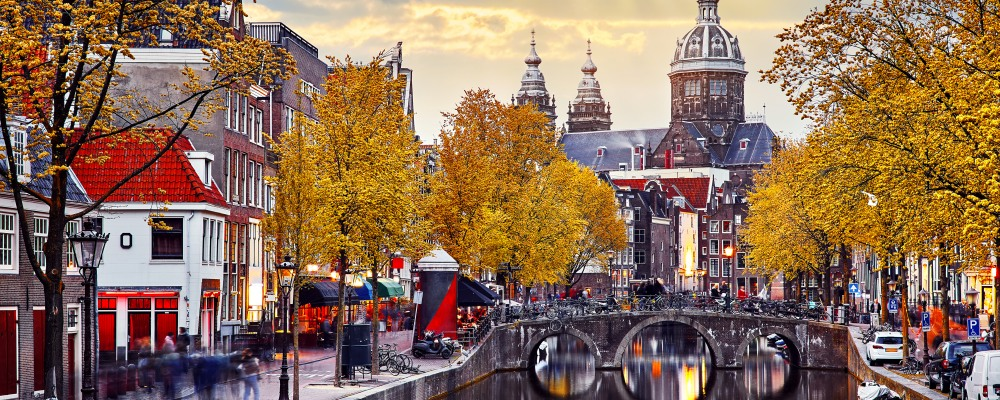 Autumn sunset in Red-light district. View at Church saint Nicholas above bridge canal with boats