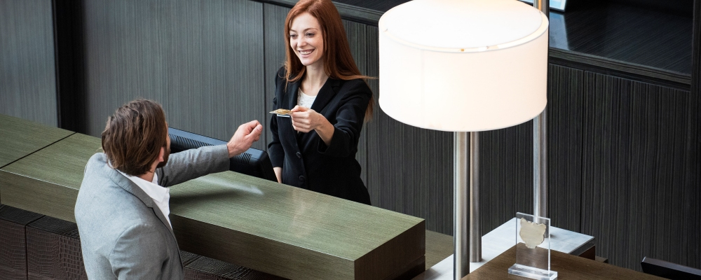 Female receptionist giving credit card to businessman