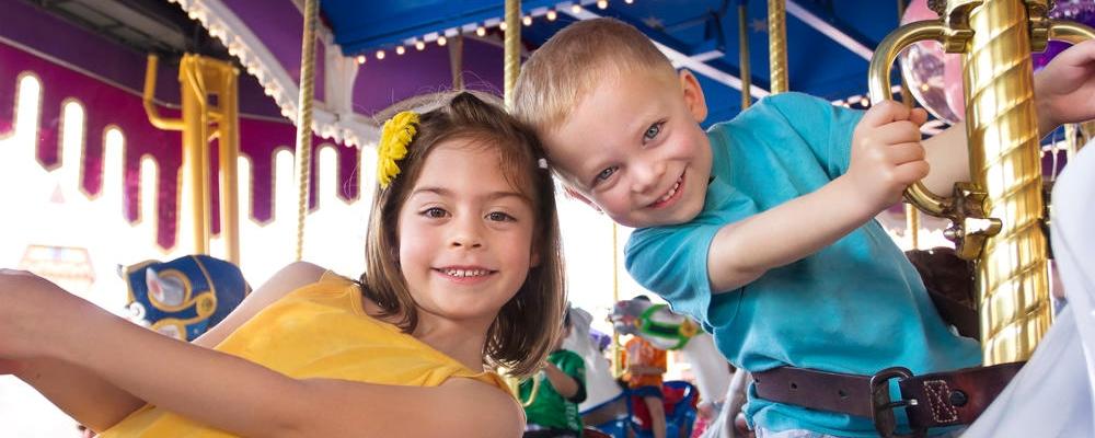 kids having fun while riding a carousel at an amusement park or carnival