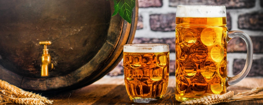 Beer glasses and beer barrel with wheat on wooden table