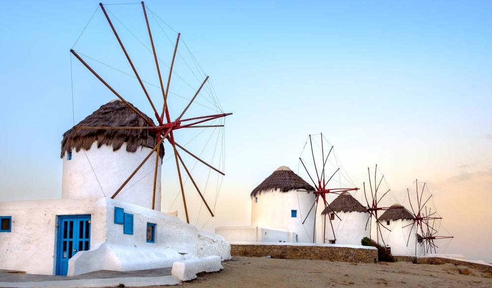 Scenic view of traditional greek windmills on Mykonos island at sunrise,
