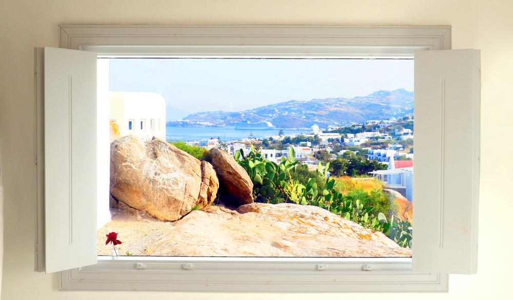 Magical white window offering a beautiful view of the island of Mykonos