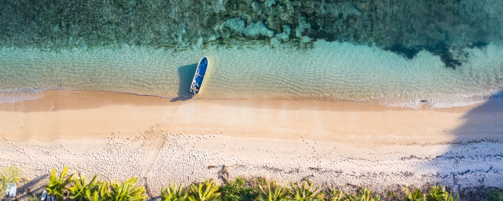 view of an idyllic island with a boat, palm trees and coral reef in Fiji
