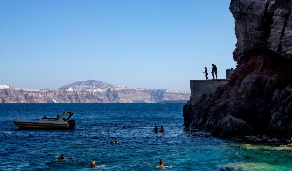 Cliff diving and swimming in Santorini Oia Amoudi