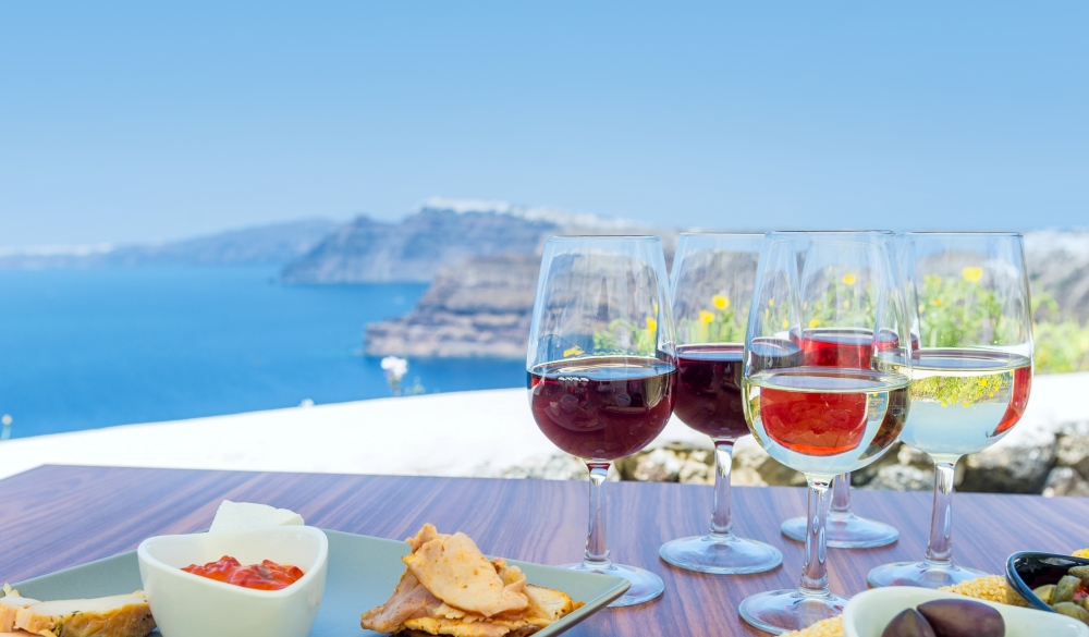 Tasting red, white and rose wine. Sea view in the background.