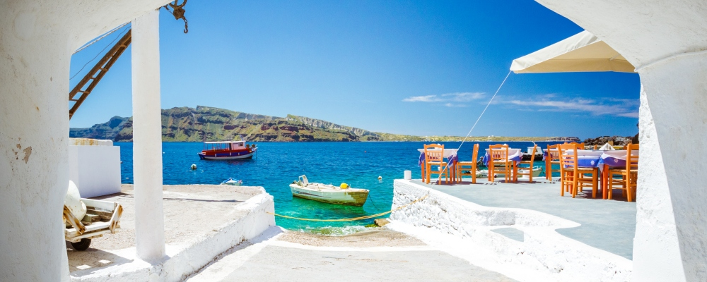 The old harbor of Ammoudi under the famous village of Oia at Santorini, Greece through a frame of an old arched building