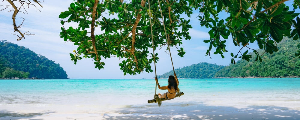 girl on swing in the tropical beach island paradise