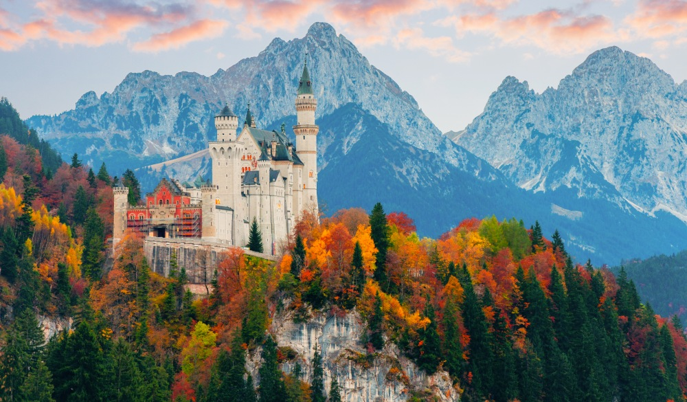 Picturesque autumn view on Neuschwanstein Castle with colorful trees and the Alps on background, Bavaria, Germany. Beautiful autumn colorful scenery.;