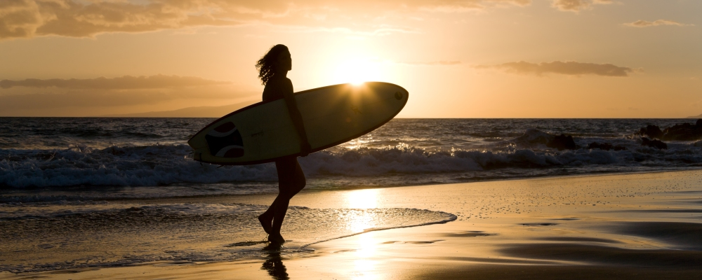 woman with surfboard at sunset in Hawaii