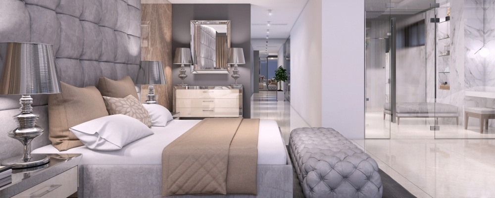 Luxury hotel like bedroom interior with large bed, seat, and terrace. expensive marble wall and large bathroom with glass wall.