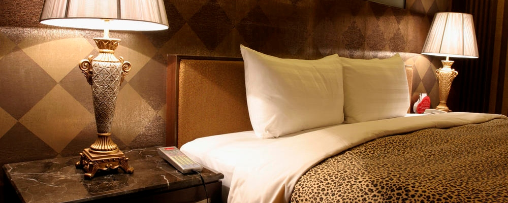 Double bed in hotel room with warm light