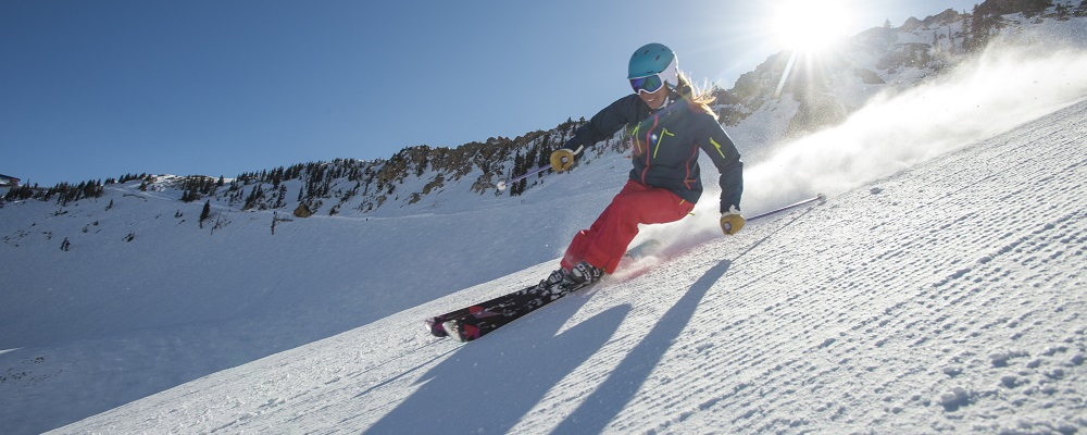 A woman skiing on a sunny winter day at Snowbird