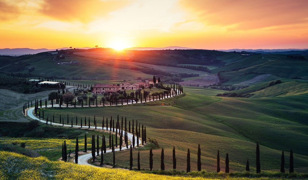 Tuscany landscape with winding country road at sunset