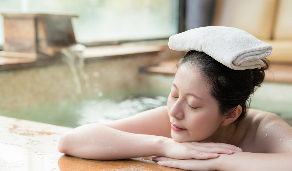 japanese girl lying down on poolside sleep and put a towel on her head while water flows on the background.