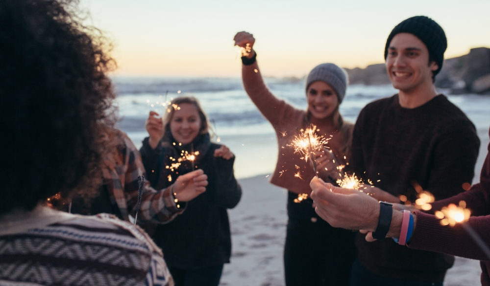 young people celebrating new year's day at the beach