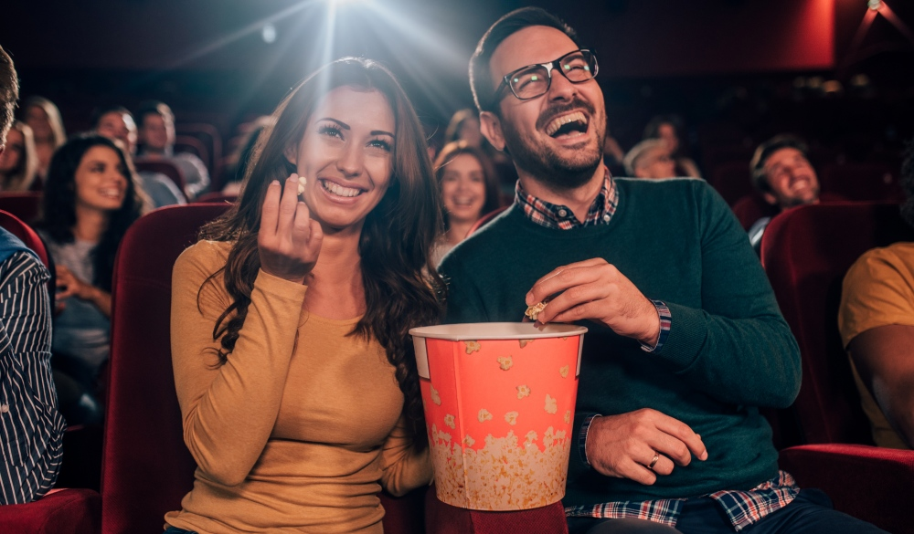 young friends eating popcorn in the cinema