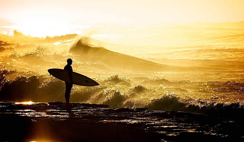 Silhouette of surfer holding surfboard on rocks on Merewether beach.