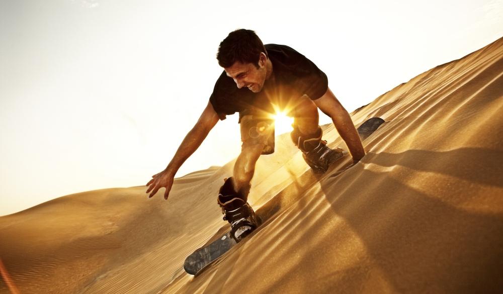 man sand boarding on the sand dune called Big Red in the desert near Dubai