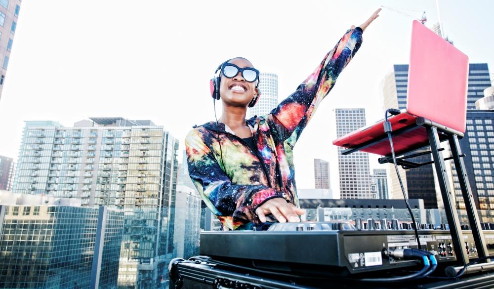Smiling Black DJ on urban rooftop, cinco de Mayo celebration