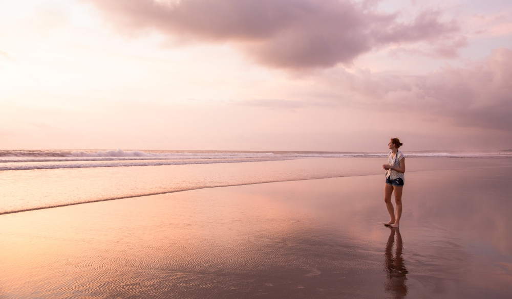 The Beach between Legian and Seminyak just before sunset. One attractive young woman is walking on the sandy beach in the shallow waters. Seminyak beach, Kuta, Bali, Indonesia.