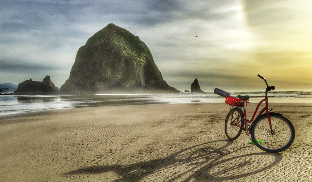 Haystack Rock with the shadow from a red bicycle on the shoreline of Cannon Beach, Oregon.