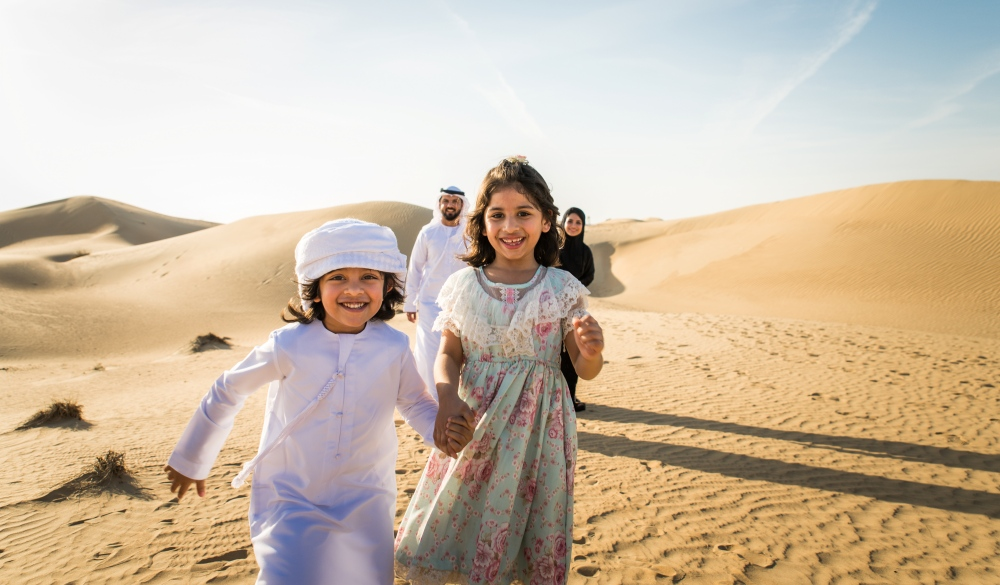 Arabian family with kids having fun in the desert
