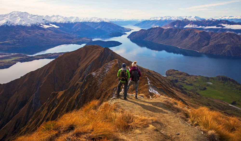 Two young women climb up and look out over the viewpoint at the top of Mt. Roy in New Zealand
