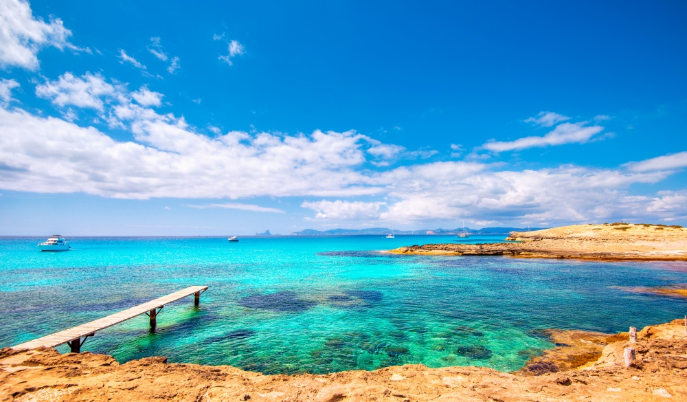 Jetty and private boats at Formentera´s most beautiful and famous beach, Playa de ses Illetes.