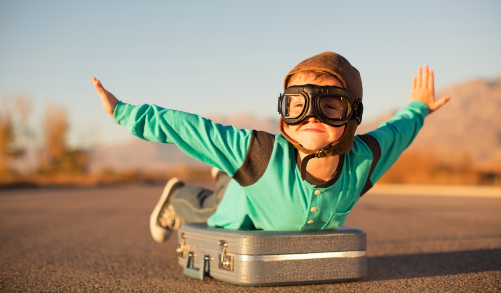 A young boy with outstretched arms lies on top of a suitcase imagining he is flying on an airplane away and traveling to exotic locations. He is wearing a flight cap and goggles and has a large smile on his face. He loves to travel.