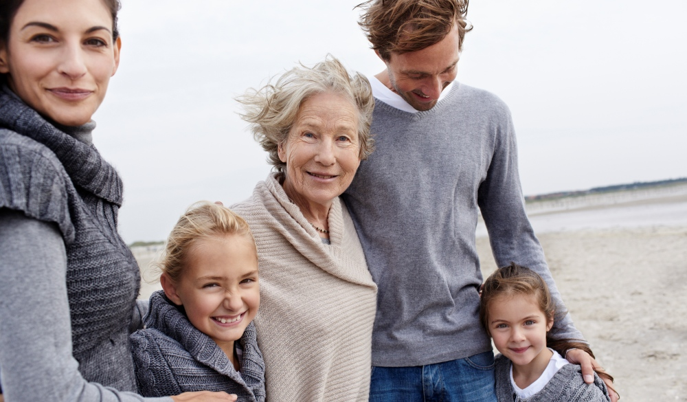 Happy family with grandmother on the beach, mother's day getaway