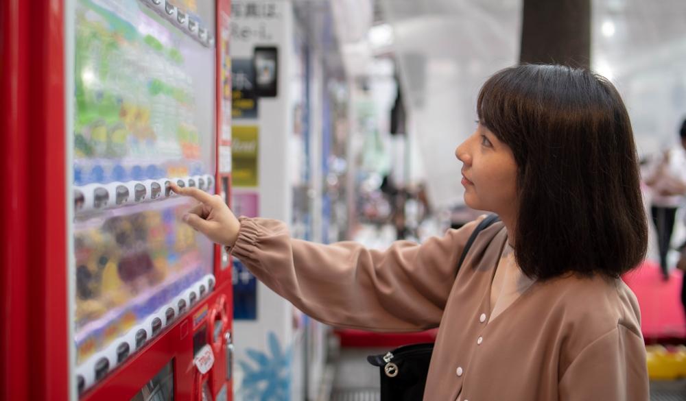 Young woman touching button on vending machine, things to do in Akihabara