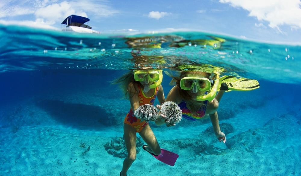 Cayman Islands, girls snorkeling holding sea urchins, boat above