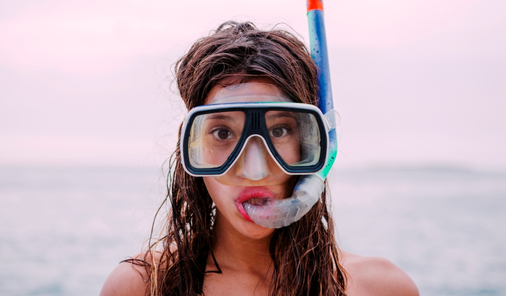 Young woman with diving goggles and snorkel