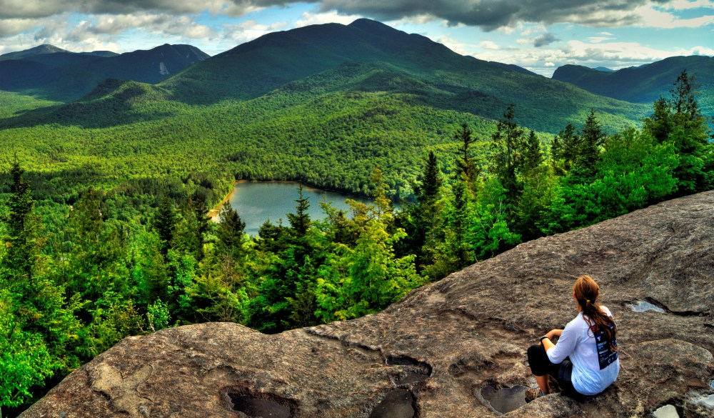 hiker takes in the view of the Adirondack High Peaks, underrated U.S. destinations