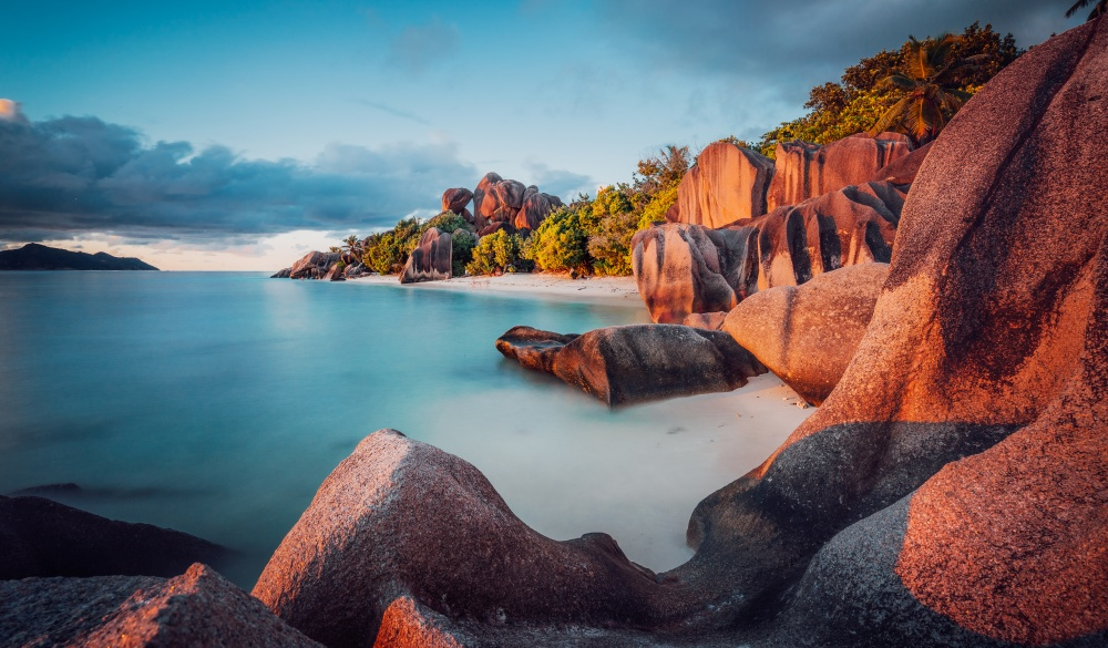 boulders and a dramatic sunset at Anse Source d'Argent beach, La Digue island, tropical island vacations