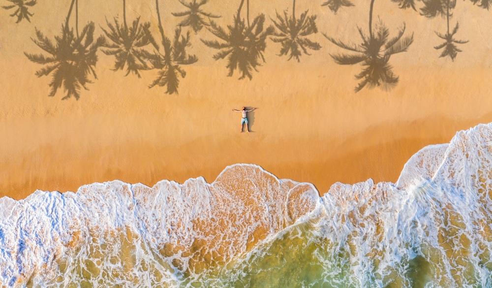 a man lies on a sandy beach on a tropical island, vacations