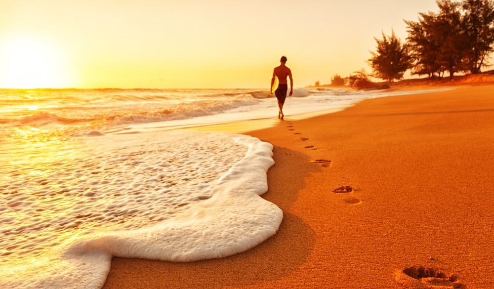 a surfer walking into the water with his surf board, tropical island vacations