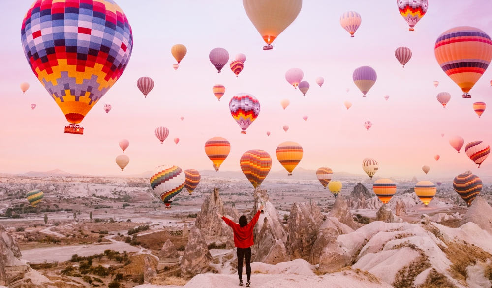 Young woman on a background of flying balloons at sunrise in Cappadocia