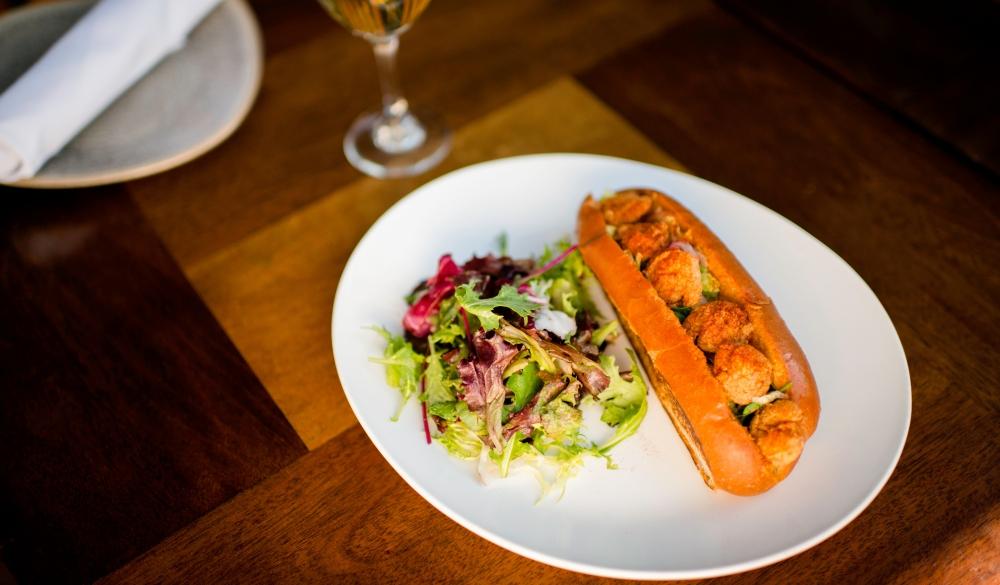 Plate of fried shrimp poboy sandwich on restaurant table