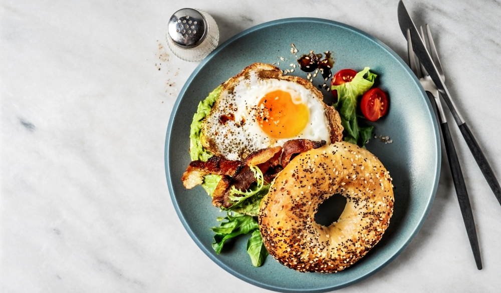 Bagel sandwich with avocado, fried egg and side salad on white background