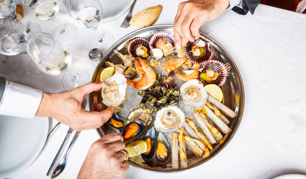 seafood plate and male hands picking food