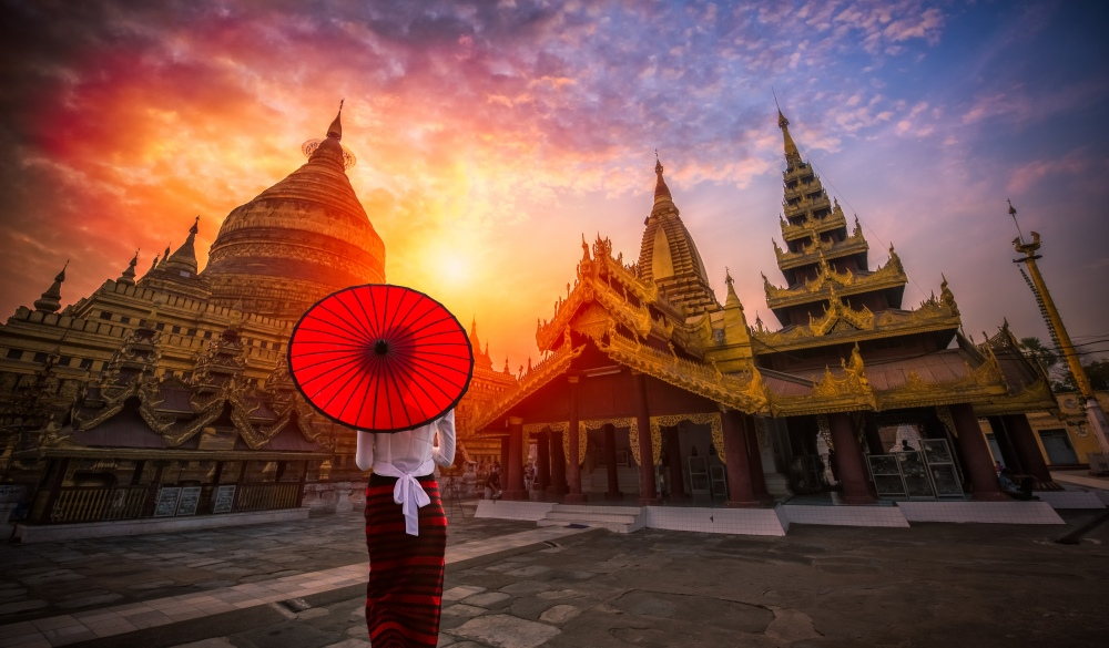 Burmese woman holding traditional red umbrella and looks at Golden Shwezigon pagoda in Bagan, Myanmar
