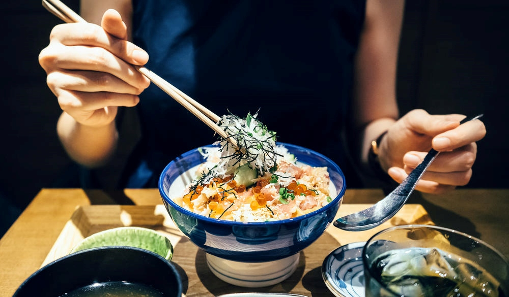 woman enjoying freshly served traditional Japanese seafood donburi