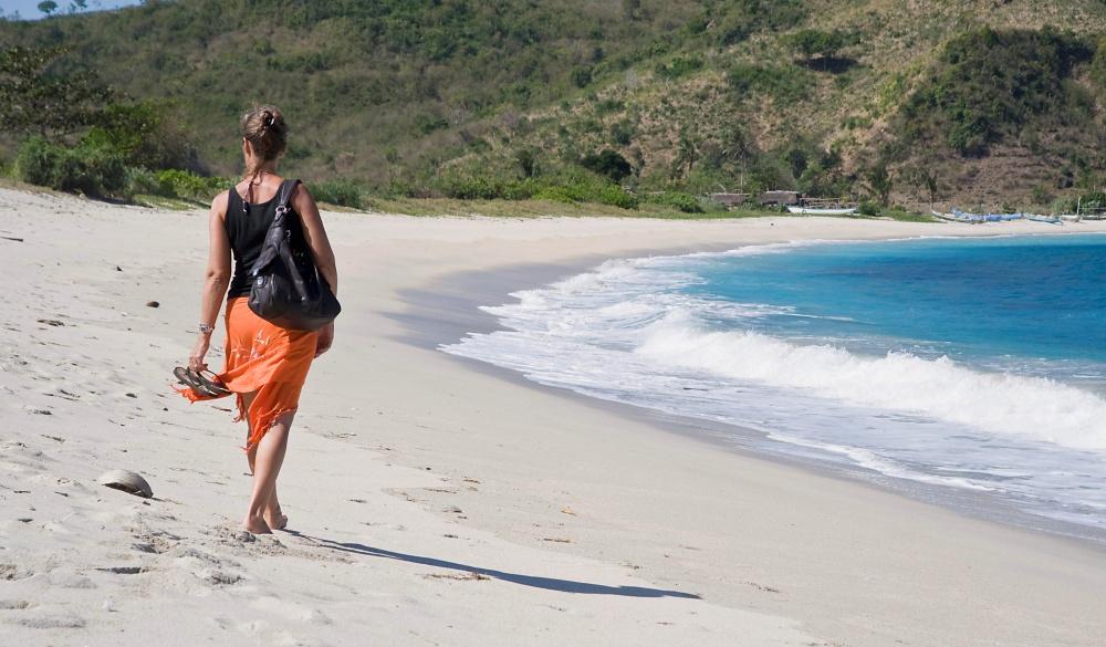 Woman walking along a deserted sandy beach, Kuta, Lombok, Indonesia, Southeast Asia