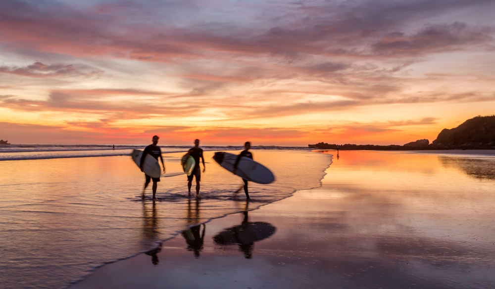 Surfers at sunset walking on beach, Costa Rica