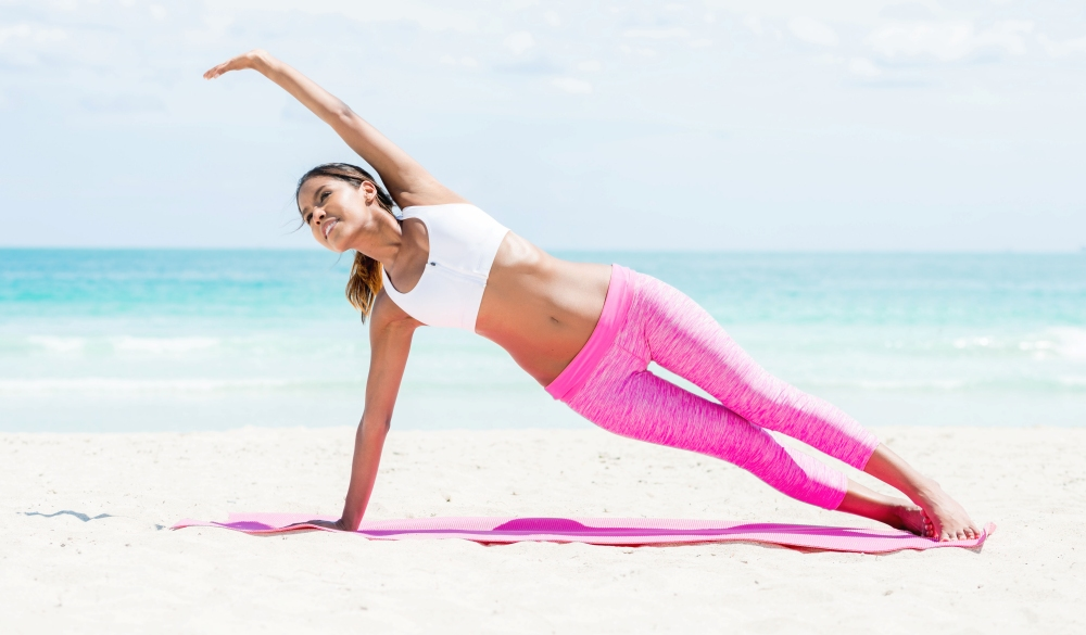 Fit woman doing yoga at Miami beach w